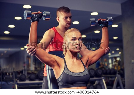 sport, fitness, bodybuilding, lifestyle and people concept - man and woman with dumbbells flexing muscles in gym - stock photo