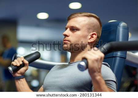 sport, fitness, bodybuilding, lifestyle and people concept - man exercising and flexing muscles on gym machine