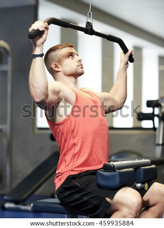 sport, fitness, bodybuilding, lifestyle and people concept - man exercising and flexing muscles on cable machine in gym - stock photo