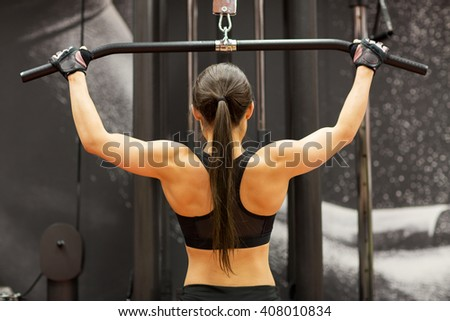 sport, fitness, bodybuilding, lifestyle and people concept - woman flexing muscles on cable machine in gym - stock photo