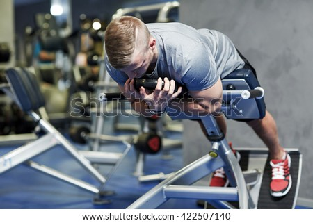 sport, fitness, bodybuilding, lifestyle and people concept - young man flexing back and abdominal muscles on bench in gym - stock photo