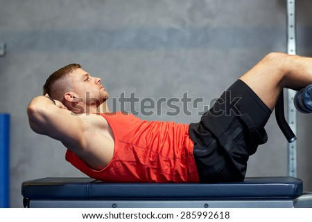 sport, fitness, bodybuilding, lifestyle and people concept - young man making abdominal exercises in gym - stock photo