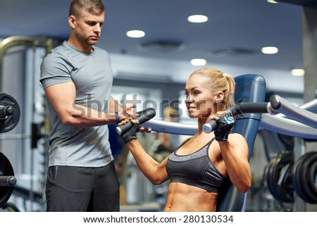 sport, fitness, bodybuilding, teamwork and people concept - young woman and personal trainer flexing muscles on gym machine - stock photo