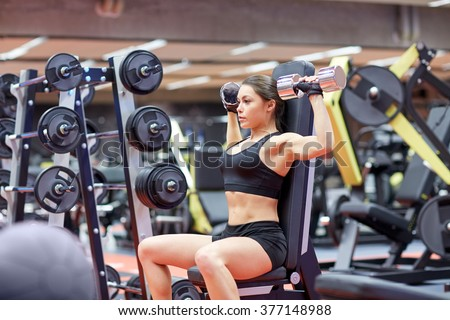 sport, fitness, bodybuilding, weightlifting and people concept - young woman with dumbbell flexing muscles in gym from back - stock photo