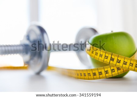 sport, fitness, diet and objects concept - close up of dumbbell and green apple with measuring tape - stock photo
