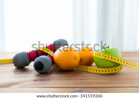 sport, fitness, diet and objects concept - close up of dumbbell and green apple with oranges wrapped by measuring tape on wooden table - stock photo