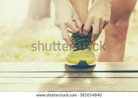 sport, fitness, exercise and lifestyle concept - runner man lacing trainers shoes - stock photo