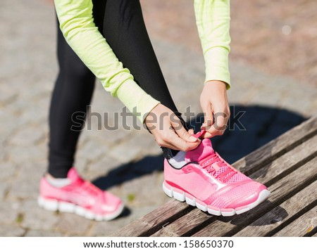sport, fitness, exercise and lifestyle concept - runner woman lacing trainers shoes - stock photo
