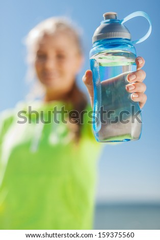 sport, fitness, exercise, nutrition and lifestyle concept - woman showing a bottle of water after doing sports outdoors - stock photo