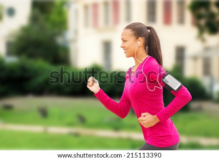 sport, fitness, health, technology and people concept - smiling young african american woman running with smartphone and earphones outdoors - stock photo