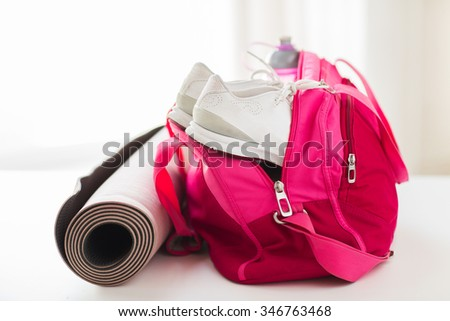 sport, fitness, healthy lifestyle and objects concept - close up of female sports stuff in bag - stock photo