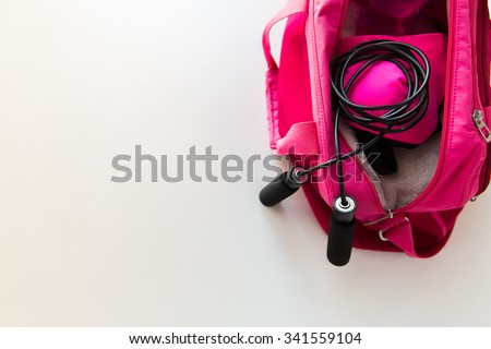 sport, fitness, healthy lifestyle and objects concept - close up of female sports stuff in bag and skipping rope - stock photo