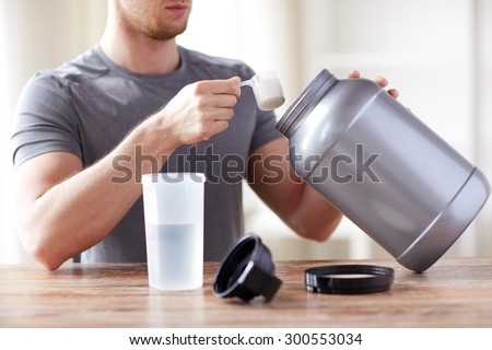 sport, fitness, healthy lifestyle and people concept - close up of man with jar and bottle preparing protein shake - stock photo
