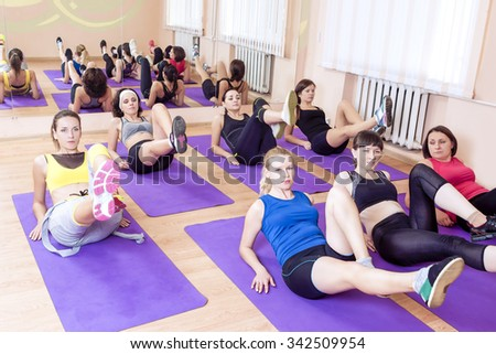 Sport, Fitness, Healthy Lifestyle Concepts. Group of Caucasain Women Having Stretching Workout Indoors on a Purple Sport Mats. Horizontal Image Composition - stock photo