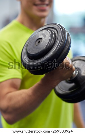 sport, fitness, lifestyle and people concept - close up of smiling man with dumbbell flexing biceps in gym - stock photo