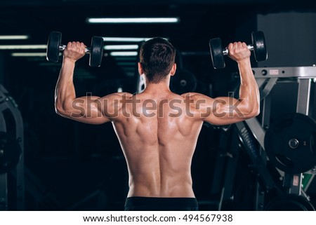 sport, fitness, lifestyle and people concept - Muscular bodybuilder guy doing exercises with dumbbells in gym.