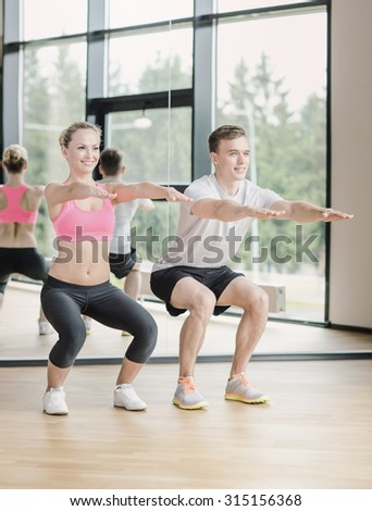 sport, fitness, lifestyle and people concept - smiling man and woman exercising in gym