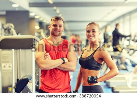 sport, fitness, lifestyle and people concept - smiling man and woman in gym - stock photo