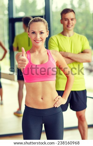 sport, fitness, lifestyle and people concept - smiling man and woman showing thumbs up in gym - stock photo