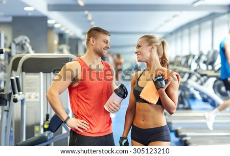 sport, fitness, lifestyle and people concept - smiling man and woman with protein shake bottle and towel talking in gym - stock photo