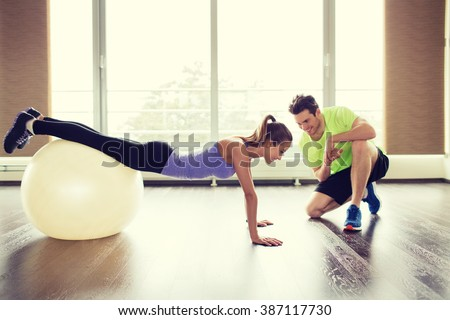 sport, fitness, lifestyle and people concept - smiling man and woman working out with exercise ball in gym - stock photo
