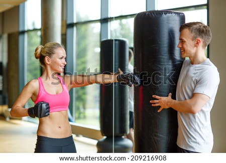 sport, fitness, lifestyle and people concept - smiling woman with personal trainer boxing in gym - stock photo
