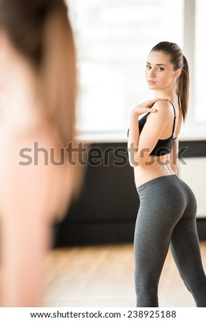 Sport, fitness, lifestyle concept. Beautiful woman in gym is looking at the mirror. - stock photo