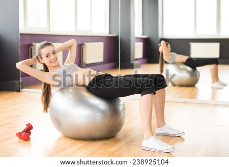 Sport, fitness, lifestyle concept. Smiling woman with exercise ball in gym is looking at the camera. - stock photo