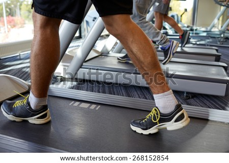 sport, fitness, lifestyle, technology and people concept - close up of men legs walking on treadmills in gym - stock photo