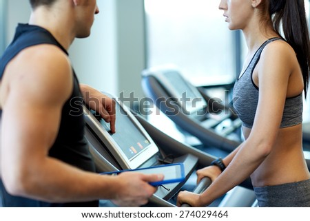 sport, fitness, lifestyle, technology and people concept - close up of woman with trainer working out on treadmill in gym - stock photo