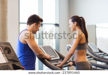 sport, fitness, lifestyle, technology and people concept - happy woman with trainer working out on treadmill in gym - stock photo