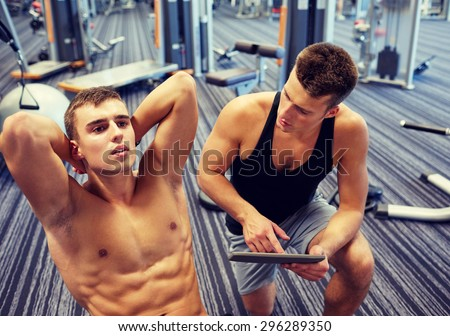 sport, fitness, lifestyle, technology and people concept - man and personal trainer with tablet pc computer and flexing abdominal muscles in gym - stock photo