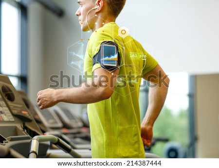 sport, fitness, lifestyle, technology and people concept - man with smartphone and earphones exercising on treadmill in gym - stock photo