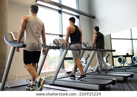 sport, fitness, lifestyle, technology and people concept - men exercising on treadmill in gym - stock photo