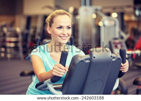 sport, fitness, lifestyle, technology and people concept - smiling woman exercising on exercise bike in gym - stock photo