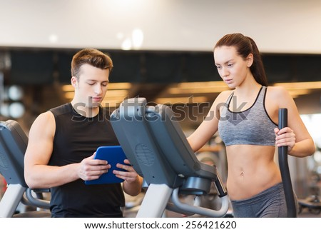 sport, fitness, lifestyle, technology and people concept - woman with trainer exercising on stepper in gym - stock photo