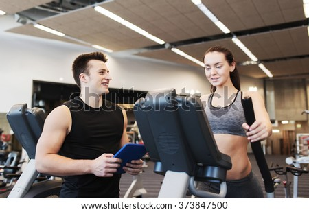 sport, fitness, lifestyle, technology and people concept - woman with trainer exercising on stepper in gym