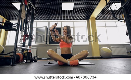 sport, fitness, lifestyle, technology and people concept - young woman with smartphone taking selfie in gym - stock photo