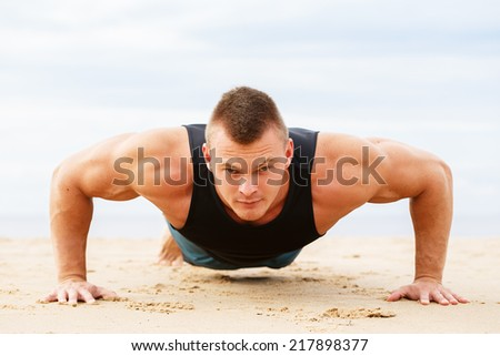 Sport, fitness. Man doing push-up on the beach