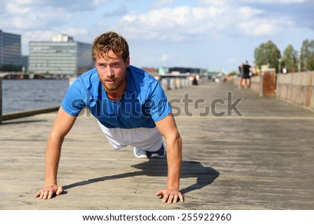 Sport fitness man push-ups. Male athlete exercising push up outside in urban city boardwalk. Fit male fitness model in crossfit exercise outdoors. Healthy lifestyle in Bryggen, Copenhagen, Denmark - stock photo