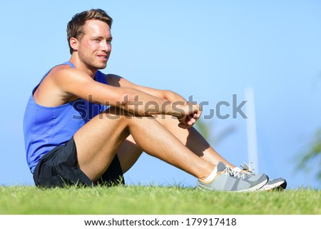 Sport fitness man relaxing after training outdoor. Young male athlete resting relaxing sitting in grass after running and training exercise outside in summer. Caucasian man sports model. - stock photo