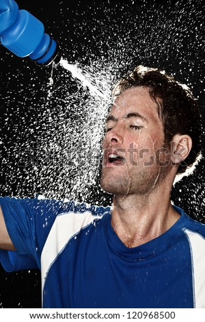 Sport fitness man. Studio shot of a young athletic man cooling himself after training by squirting water over himself from a drinks bottle - stock photo