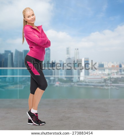 sport, fitness, people and weight loss concept - beautiful sporty young woman over city waterside background - stock photo