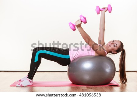 Sport, fitness, people, gym concept. Happy lady doing some workout. Beautiful girl has nice sporty outfit.