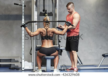 sport, fitness, teamwork and people concept - young woman and personal trainer flexing muscles on gym machine - stock photo