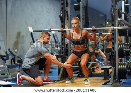 sport, fitness, teamwork, bodybuilding and people concept - young woman and personal trainer with barbell flexing muscles in gym - stock photo