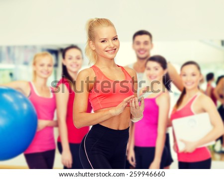 sport, fitness, technology, internet and healthcare concept - smiling sporty woman with smartphone - stock photo