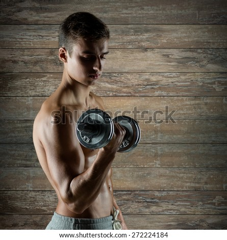 sport, fitness, weightlifting, bodybuilding and people concept - young man with dumbbell flexing biceps over wooden wall background - stock photo