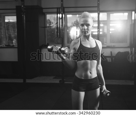 Sport. Fitness. Woman. Black and white image. Young girl at the gym. Exercise three pound dumbbells. Coaching arm muscles. Evening classes in fitness room. Sports hall. Advertising concept for gym.