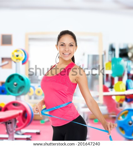 sport fitness woman in gym smile measure waist with tape, young healthy perfect slim figure - stock photo